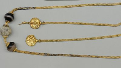 A necklace measuring almost 80cm was found near the neck of the warrior's skeleton. It features two gold pendants decorated with ivy leaves. (University of Cincinnati)