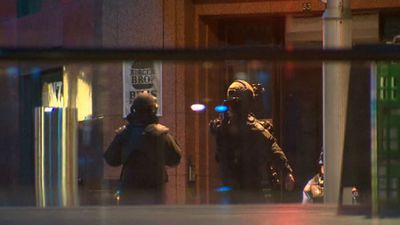 Two Special Operations Group officers stand by the Lindt cafe in Martin Place, nine hours after two female hostages escaped. (9NEWS)