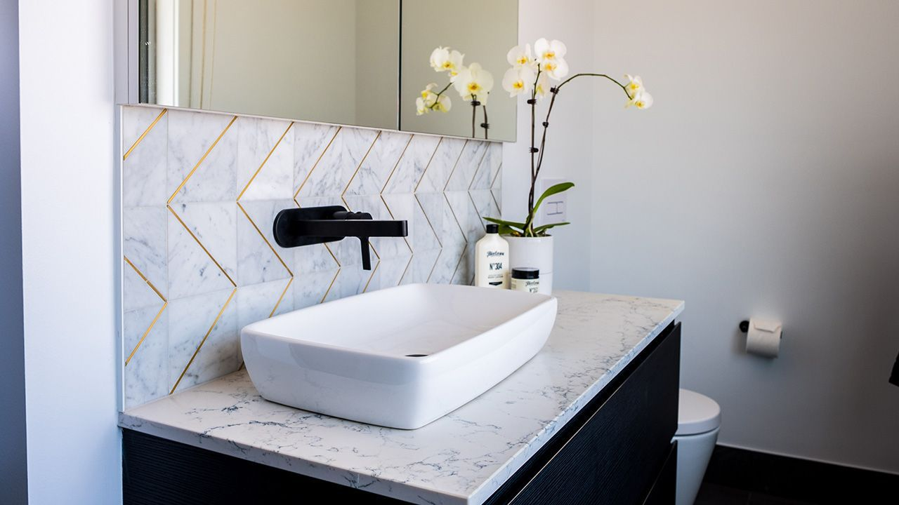 AFTER: A perfect bathroom with herringbone tiles and black taps