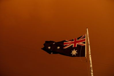 The Australia Flag flies under red skies from the fires on January 04, 2020 in Bruthen Australia, in East Gippsland. (Photo by Darrian Traynor/Getty Images)