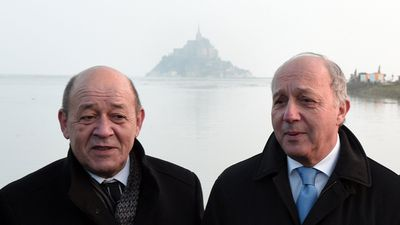 Defence minister Jean-Yves Le Drian (L) and French Foreign Affairs minister Laurent Fabius stand next to the Mont-Saint-Michel during high tide.