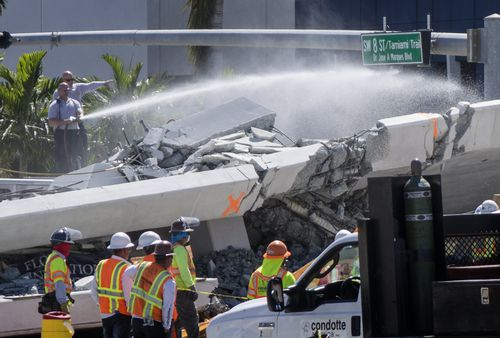 A firefighter hoses down a section of the bridge as authorities work to clear the rubble. (AAP)