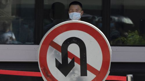 "A Chinese security person stands on duty near a ""No U-Turn"" sign outside the former United States Consulate in Chengdu in southwest China's Sichuan province."