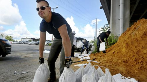 Kevin Orth loads sandbags into cars on Milford Street as he helps residents prepare.