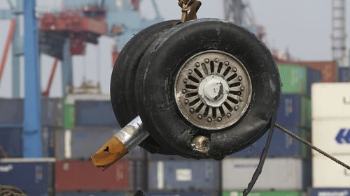 A crane moves a pair of wheels recovered from the Lion Air jet that crashed into the Java Sea.
