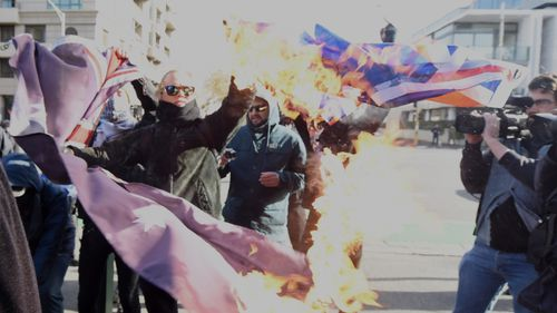 Protesters burned an Australian flag in Melbourne. (AAP)