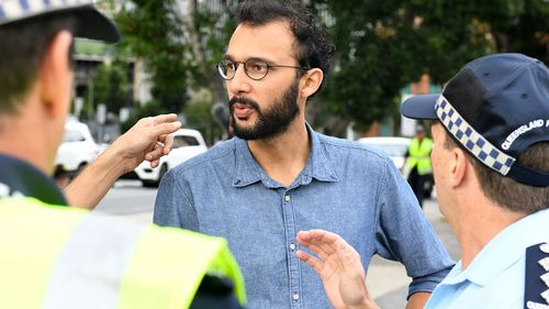 Local councillor Jonathan Sri speaks with police. (AAP)