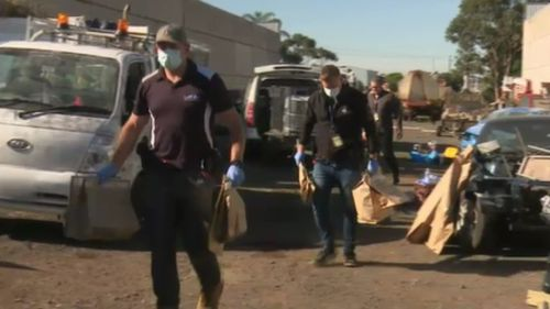 Police walk bags of evidence from the scene. (9NEWS)