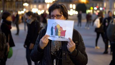 """<p>A woman holds a drawing by French cartoonist Plantu, outside the Hotel de Ville in Paris. </p><p>Dozens of cartoonists have <a href=""""http://www.9news.com.au/world/2016/03/23/06/55/brussels-attacks-cartoonists-show-solidarity-with-belgium"""">released drawings in tribute</a> to the Brussels attacks victims. (AFP)</p>"""