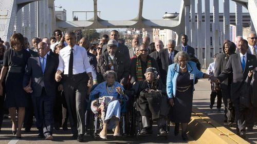John Lewis crosses the Edmund Pettus Bridge in Selma with Barack and Michelle Obama in 2015.