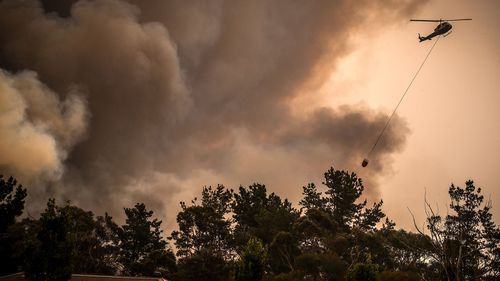 Helicopters dump water on bushfires as they approach homes located on the outskirts of the town of Bargo on December 21, 2019