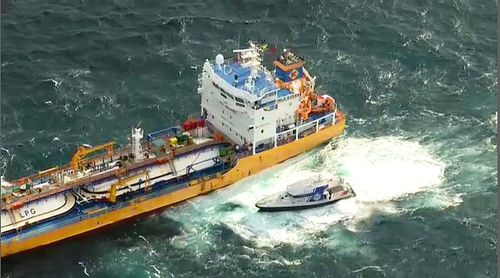 Queensland Water Police pulling alongside the Inge Kosan, following reports one crew member will be bought into hotel quarantine.