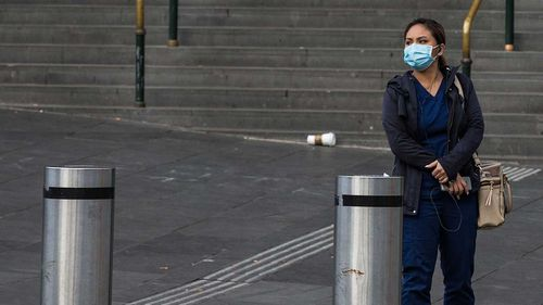 A woman wearing a face mask is seen on a very quiet Flinders Street in Melbourne.