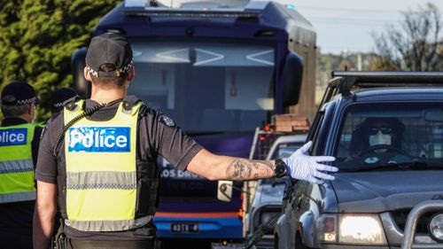 Victoria Police members stop motorists leaving metropolitan Melbourne at a checkpoint set up on the on the Calder Freeway