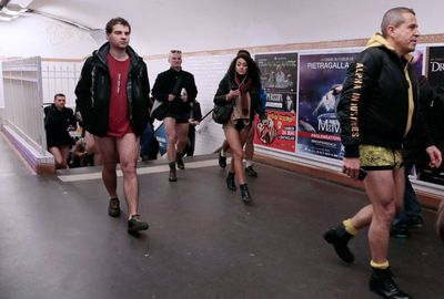 People in underwear walk in a corridor of a Paris subway station.