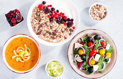 Unprocessed healthy foods, including soup, oats, berries, fresh salad