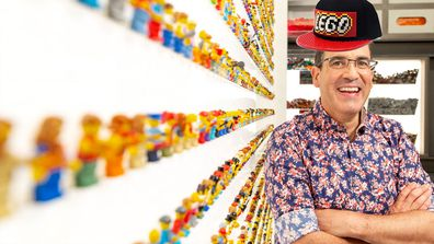 Brickman next to a wall of minifigs on LEGO Masters 2020.