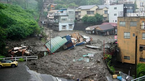 Houses are damaged by mudslide following heavy rain at Izusan district in Atami, west of Tokyo, Saturday, July 3, 2021.
