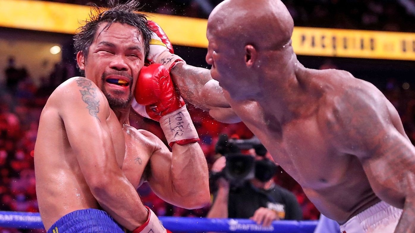 Manny Pacquiao (L) takes a punch from Yordenis Ugas during their WBA welterweight title fight at T-Mobile Arena