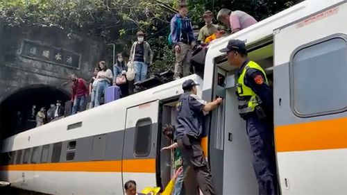 Passengers are assisted out of the train. The number of fatalities and injured was not immediately clear.