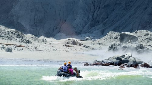 A photo provided by tourist Michael Schade shows rescuers leaving White Island following the eruption.