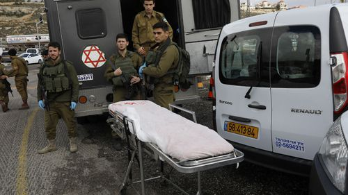 Israeli forces and medics inspect the scene of a drive-by shooting attack next to the Israeli West Bank settlement of Givat Asaf, near Ramallah