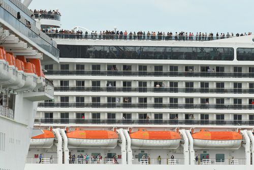 Passengers aboard the MSC Magnifica cruise ship are seen while docked alongside the Golden Princess cruise ship (left) at Station Pier in Melbourne, Thursday, March 19, 2020.