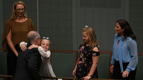 Mr Morrison is greeted by wife Jenny and daughters Abbey and Lily. (Picture: AAP)