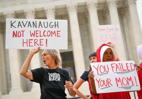 Activists protest in front of the Supreme Court in Washington as Kavanaugh takes his seat for the first time.