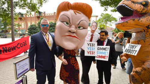 Protesters wearing masks depicting One Nation leader Pauline Hanson, Prime Minister Malcolm Turnbull and Gautam Adani are seen with a person in a dinosaur costume depicting former Prime Minister Tony Abbott outside the Queensland LNP (Liberal National Party) state convention in Brisbane in July 2018. Picture: AAP