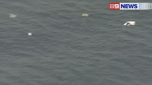 Aerial images showed debris and an oil slick on the surface of the water. (9NEWS)