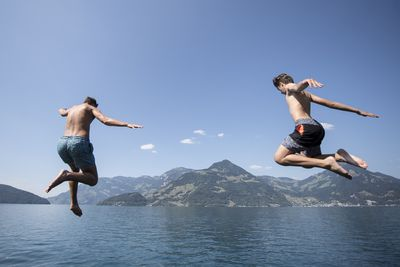 Young men jump into Lake Lucerne in Beckenried, Canton Nidwalden, Switzerland, against a spectacular backdrop.