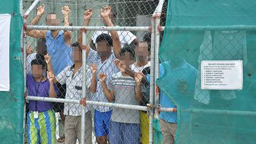 A March 21, 2014 file image of Asylum seekers staring at media from behind a fence at the Manus Island detention centre, Papua New Guinea.
