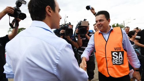 Nick Xenophon's awkward handshake with Hartley rival Vincent Tarzia on election day. (AAP)