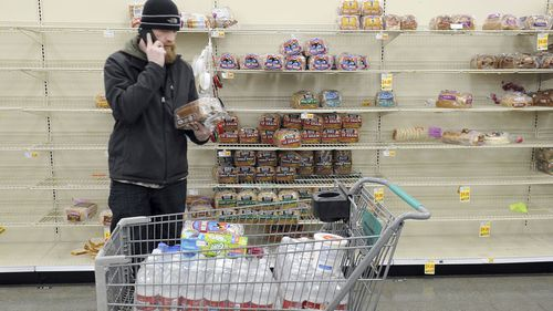 Anchorage resident C.J. Johnson stocks up on water and bread at a local grocery,