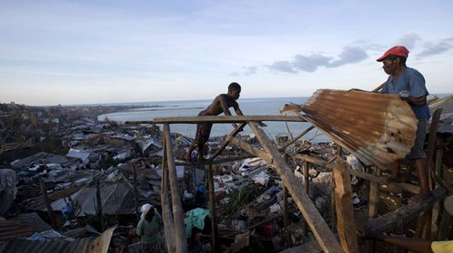Men attempt to fix corrugated roofing to the timber frame of a home in Jeremie, Haiti. (AP)