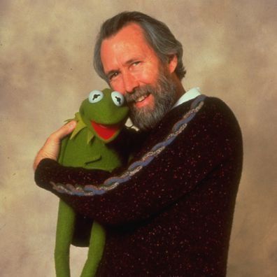 Puppeteer/creator of the Muppets Jim Henson standing with Kermit the Frog in his arms.