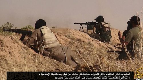 A photograph made available by the jihadist affiliated group Albaraka News allegedly shows ISIL fighters aiming at advancing Iraqi troops near the border between Syria and Iraq in 2014.