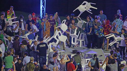Crowd members throw chairs during the Invitational Darts Challenge at Etihad Stadium in Melbourne. (Getty)
