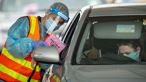 Medical professionals conduct COVID-19 tests at a drive through testing clinic in the Shepparton Sports Precinct.