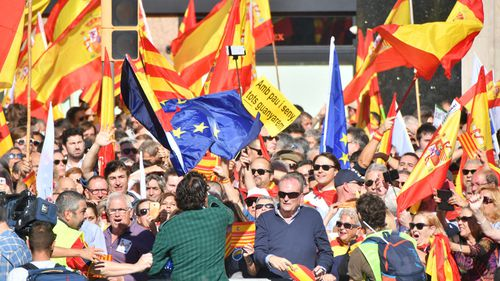 Protesters wave Spanish flags as thousands of pro-unity protesters gather in Barcelona. (AAP)