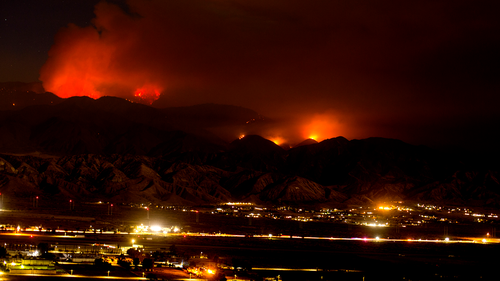 The Apple Fire burns behind mountains in Beaumont, Calif., Sunday, Aug. 2, 2020.  (AP Photo/Ringo H.W. Chiu)