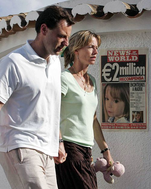 Gerry and Kate McCann pass a poster displaying their missing daughter Madeleine in the area of the beach resort of Lagos 13 May 2007, in Praia da Luz.