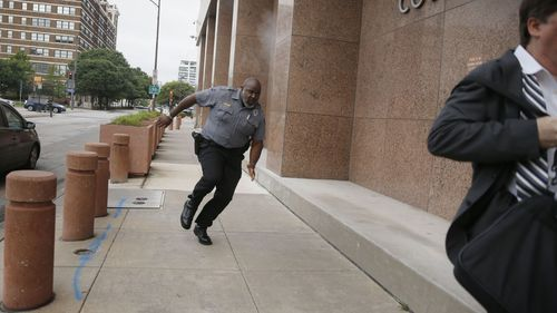 A security guard and a civilian run for cover as bullets ricochet off the building as a shooter fires towards them.