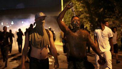 Protestors retreat from tear gas after marching toward police in Ferguson. (AAP)