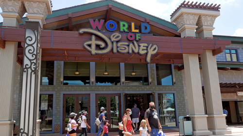 Shoppers wearing masks because of the coronavirus pandemic stroll by the World of Disney store at the Disney Springs shopping, dining and entertainment complex Tuesday, June 16, 2020, in Lake Buena Vista, Fla. (AP Photo/John Raoux)