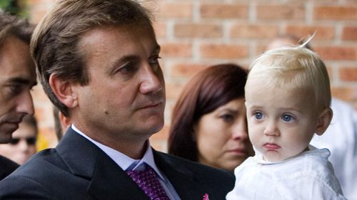 Greg McCann, pictured with baby son Cooper, at the athlete's funeral service in Wollongong in 2008. Picture: AAP