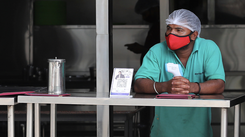 An eatery staff wearing a face mask as a precaution against coronavirus holds a thermometer as he waits to serve takeaway food to customers during lockdown in Bengaluru, India, Sunday, July 5, 2020. India's coronavirus caseload is fourth in the world behind the U.S., Brazil and Russia. (AP Photo/Aijaz Rahi)