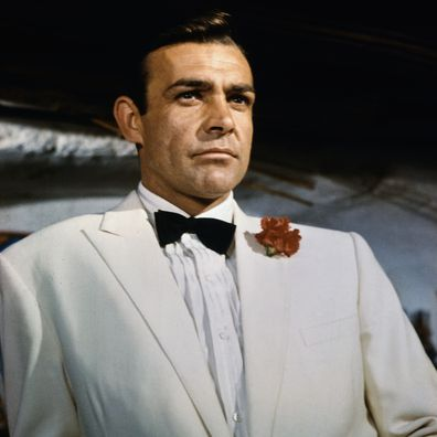 Waist-up portrait of Sean Connery, as James Bond, leaning against a bar and looking out across the room. Connery is wearing a white tuxedo and bow tie with a red carnation in his lapel. CONNERY; SEAN BOND; JAMES. 99/99/1966 35 U CT4X5