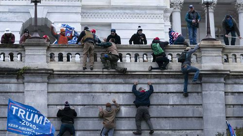 Supporters of President Donald Trump climb the West wall of the the US Capitol.